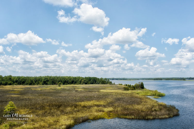 View of Blackwater River and its surrounding marsh with blue skies and some clouds as seen from I-10 west in Florida.