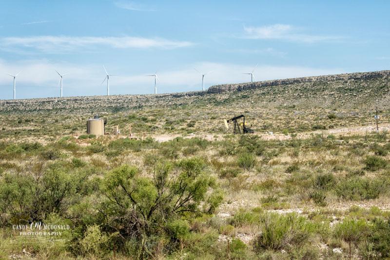 Oil derrick and wind farm in Texas' Permian Basin