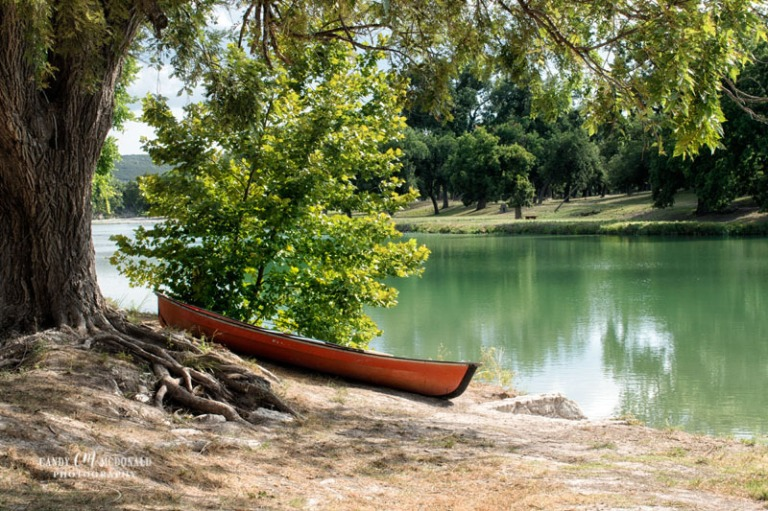 A canoe beckons along the banks of the green blue waters of the South Llano River